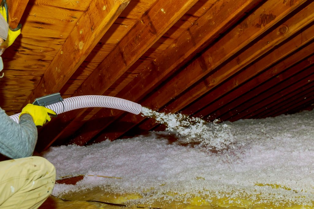 Blown In insulation technician getting the attic properly insulated
