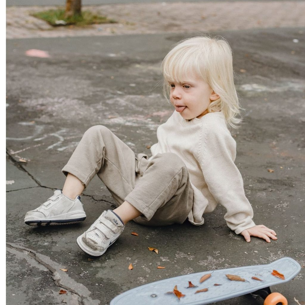 girl falls off her skateboard due to buckling concrete slabs